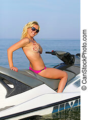 Sexy smiling young blonde on a jet ski