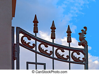 Wrought iron gate against blue sky