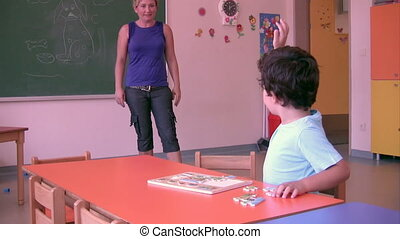 Preschool Student solving puzzle with his teacher