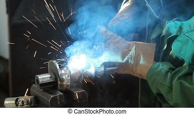 Arc Welding - Worker doing arc welding of a steel shaft with...