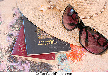 beach travel - passports on beach towel and sand with hat...