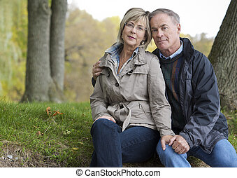 mature couple outdoors - older casual couple sitting in the...