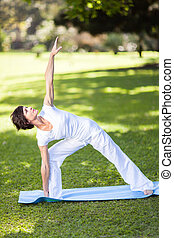 middle aged woman stretching outdoors - healthy middle aged...