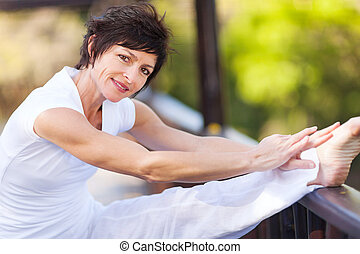 middle aged woman stretching leg - beautiful middle aged...