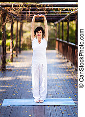 middle aged woman stretching outdoors