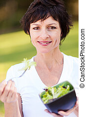 middle aged woman eating bowl of salad - healthy middle aged...