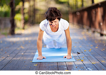 middle aged woman doing pushups outdoors