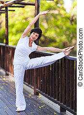 middle aged woman stretching outdoors - happy middle aged...