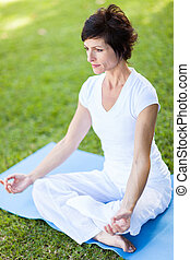 mid age woman doing yoga meditation - elegant mid age woman...
