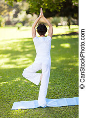 middle aged woman doing yoga outdoors - rear view of a...