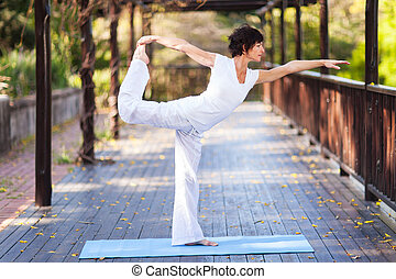 middle aged woman yoga pose outdoors
