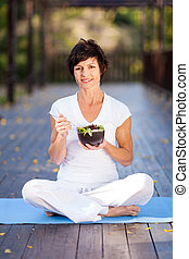 middle aged woman eating salad - healthy middle aged woman...