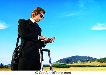 mobile phone - Handsome business man standing on a highway...