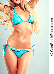 body care - Smiling young woman posing in bikini over gray...