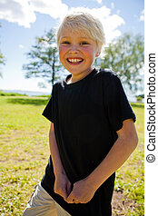 Boy outdoors - Portrait of a happy boy outdoors on a...