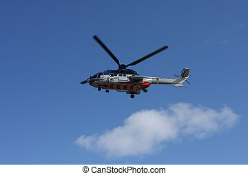 airlifting cargo - big helicopter flying overhead, blue sky...