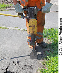 Jackhammer - Worker at site working with pneumatic plugger...