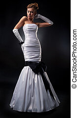 Lovely fiancee in white nuptial dress and gloves studio shot...