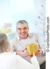 Congrats - Portrait of mature man giving present to his wife