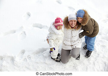 Family on snow - Happy kids and their mother on snow looking...