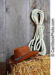 Cowboy hat on straw with ropes in a barn