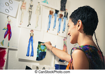 Female fashion designer contemplating drawings in studio -...