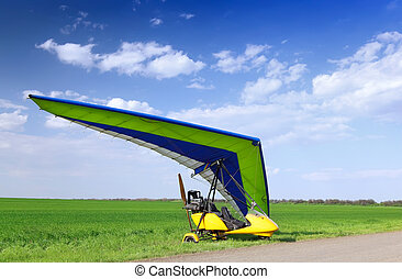 Motorized hang glider over green grass, ready to fly
