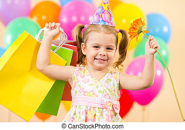 pretty child girl with colorful balloons and gifts on birthday party