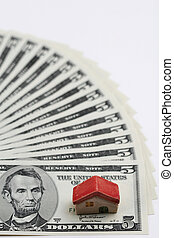 Home finances - A shallow focus of a miniature of a house on...