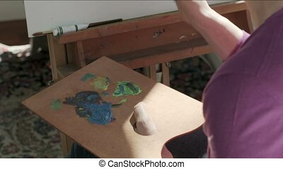 Happy elderly woman painting