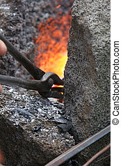 heating the stick - A craftsman/blacksmith working metal the...