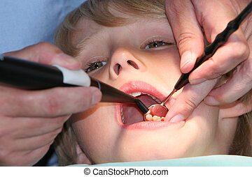 do you brush - A young boy at the dentists, dentist taking a...