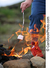 happy times - marshmallow on a stick being roasted over a...