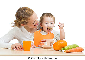 baby eating vegetables puree by spoon himself and sitting on...