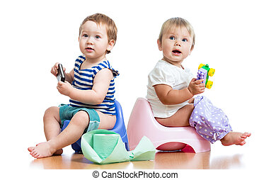 babies toddlers sitting on chamber pot and playing with toys
