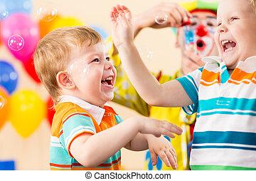 joyful kids with clown on birthday party