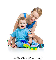 baby boy and mother playing together with construction set...
