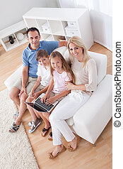 Happy Family Sitting On A Sofa Using Laptop