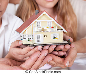 Family Sitting Holding Miniature Model Of House - Family...