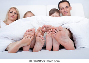 Happy Family In Bed Under Cover Showing Feet - Happy Family...