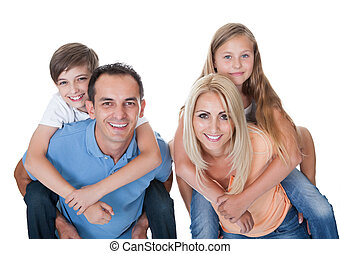 Couple Giving Two Young Children Piggyback Rides