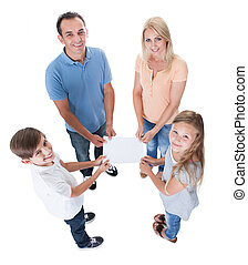 Elevated View Of Family Holding Blank Paper - Elevated View...