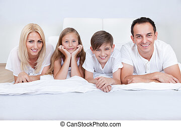 Happy Family With Two Children Lying On Bed