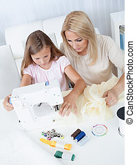 Beautiful Young Girl Sewing With Her Mother