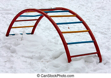 empty swing-set covered with snow in winter