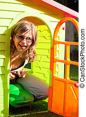 Funny woman playing in playhouse