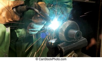 Welding - Welder doing arc welding of a steel shaft with...