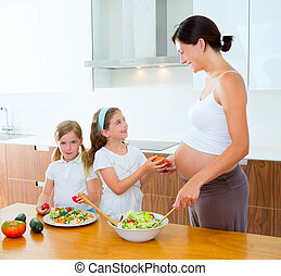 Beautiful pregnant mother with her daughters at kitchen...