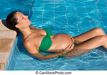 Beautiful pregnant woman sun tanning at blue pool