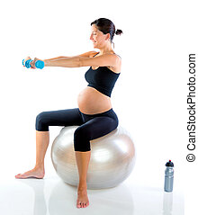 Beautiful pregnant woman at fitness gym with dumbells on...